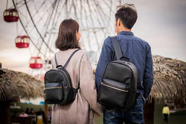 ペアリュックで遊園地を歩くカップル